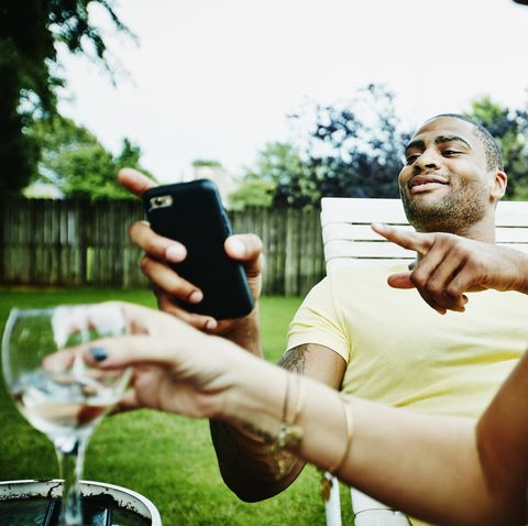 smiling man hanging out with friends in back yard on summer evening