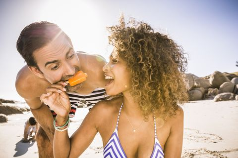 Couple sharing ice lolly on beach, Cape Town, South Africa