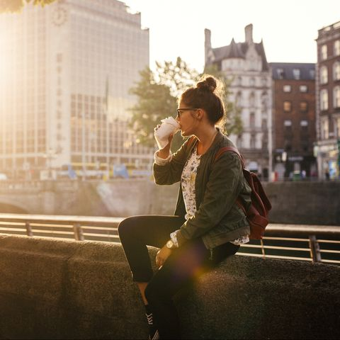 Woman drinking coffee while sitting retailing wall of bridge in city