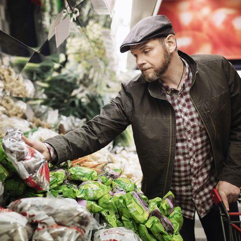 Man buying fresh vegetables in supermarket