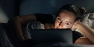 Woman using home tablet pc in bed.