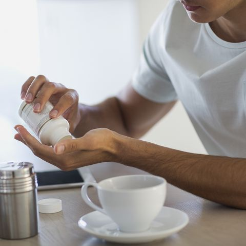 Close-up of a young man taking nutritional supplement pills