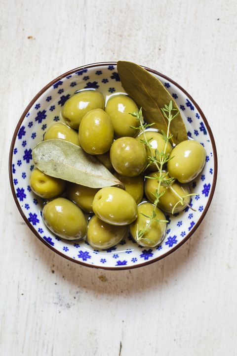 green olives in bowl with thyme and bay leaf