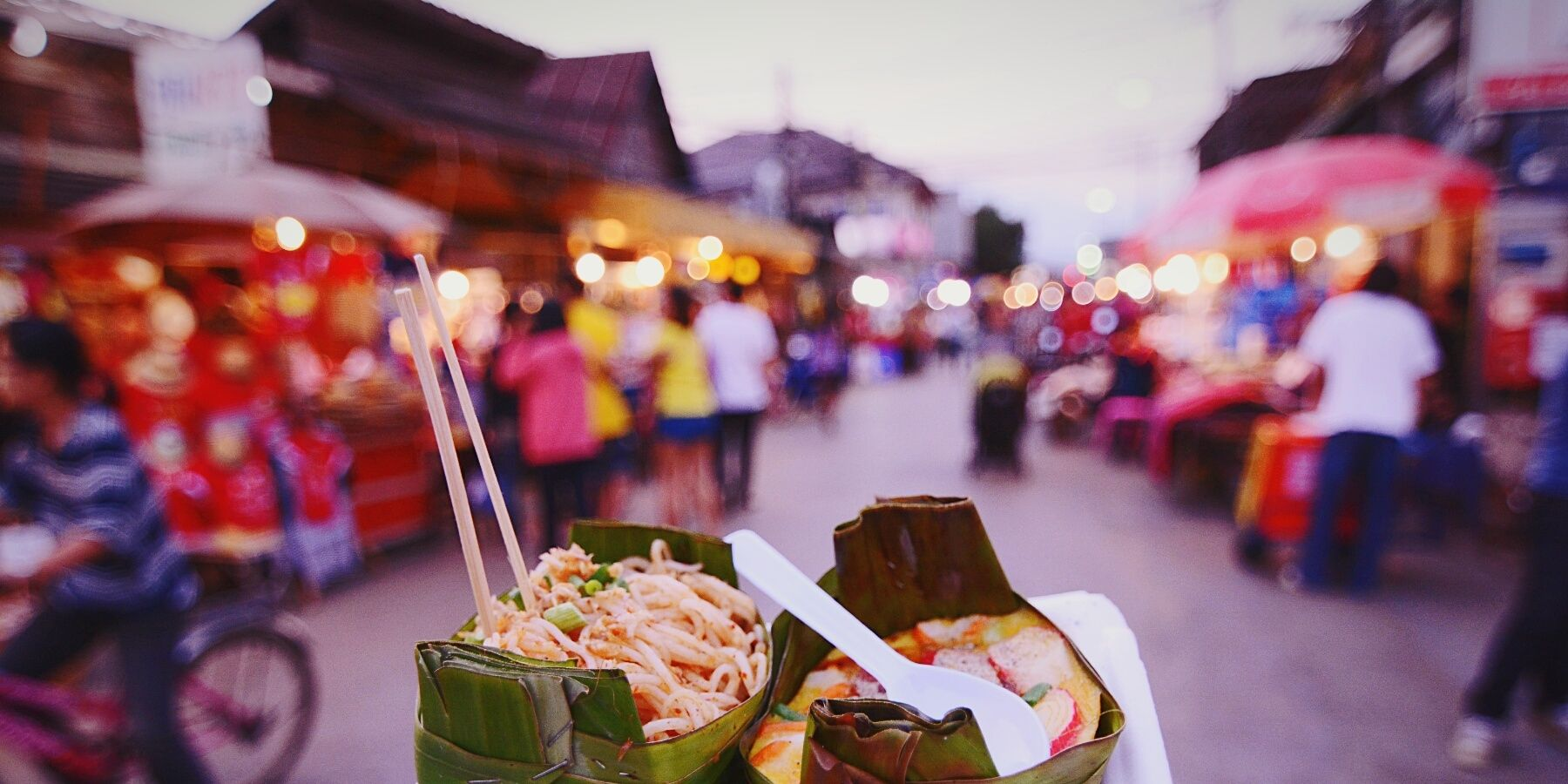 Cropped Image Of Person Holding Street Food In Market At Dusk