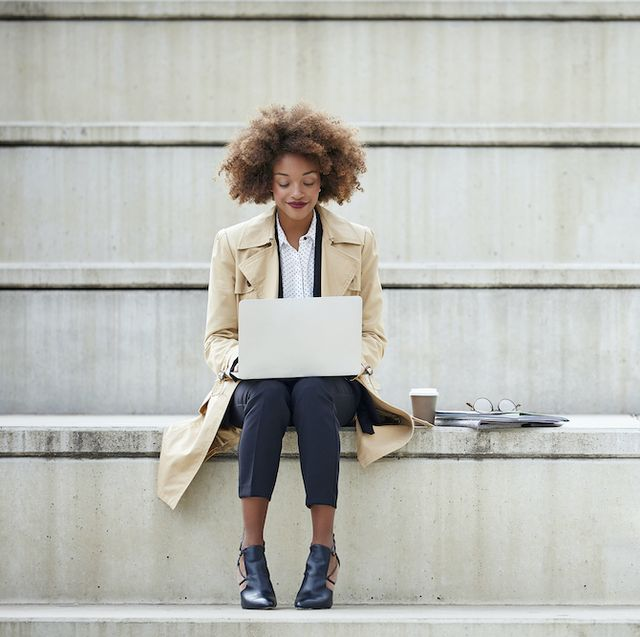 young businesswoman using laptop while sitting on steps full length of female professional working on staircase she is wearing long winter coat
