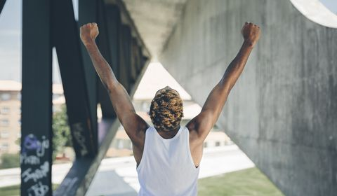 Back view of young man raising his arms