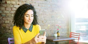 Woman using mobile in coffee shop