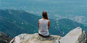 Vista de espaldas de una mujer sentada en lo alto de una montaña