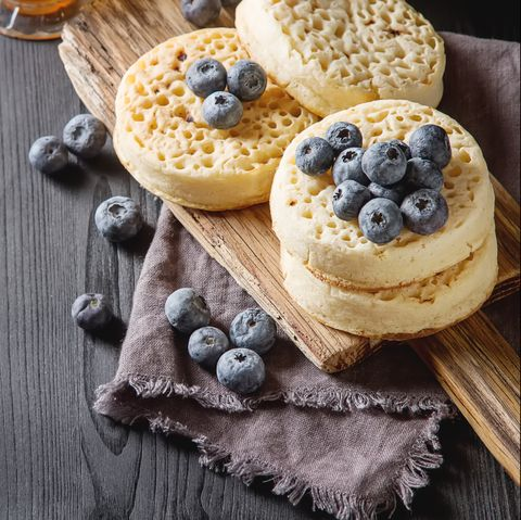 hot home made toasted crumpets served with honey, blueberry dark wood background british breakfast
