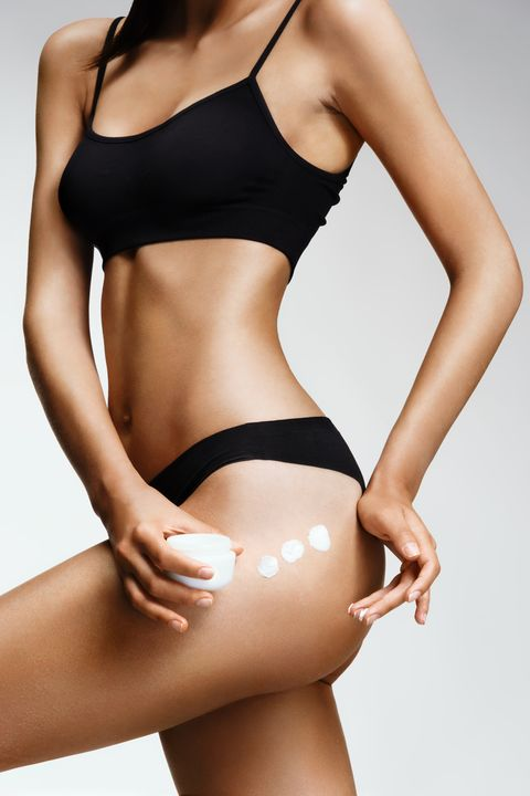 applying moisturizer cream slender woman in black lingerie cares about her buttocks beauty part of female body womans shape with clean skin skin care concept