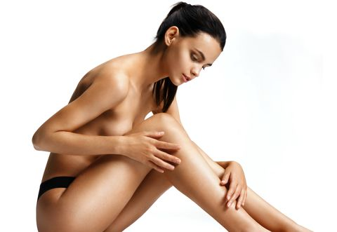 healthy naked woman with perfect body over white beautiful female sitting on the floor touch leg beauty  skin care concept