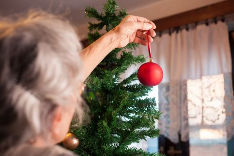 old woman putting ornaments on Christmas tree