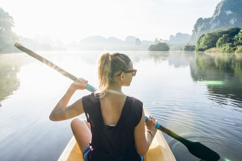 Young woman paddles kayak across jungle pond, mountains distant