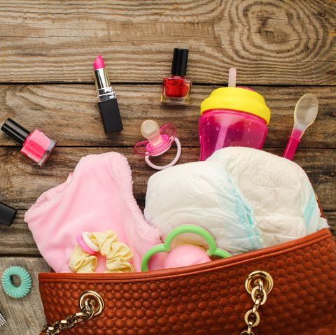 Mother's handbag with items to care for child and cosmetics on wooden background. Top view.