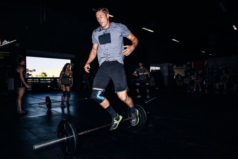 Cross training athlete jumping over barbell in gym