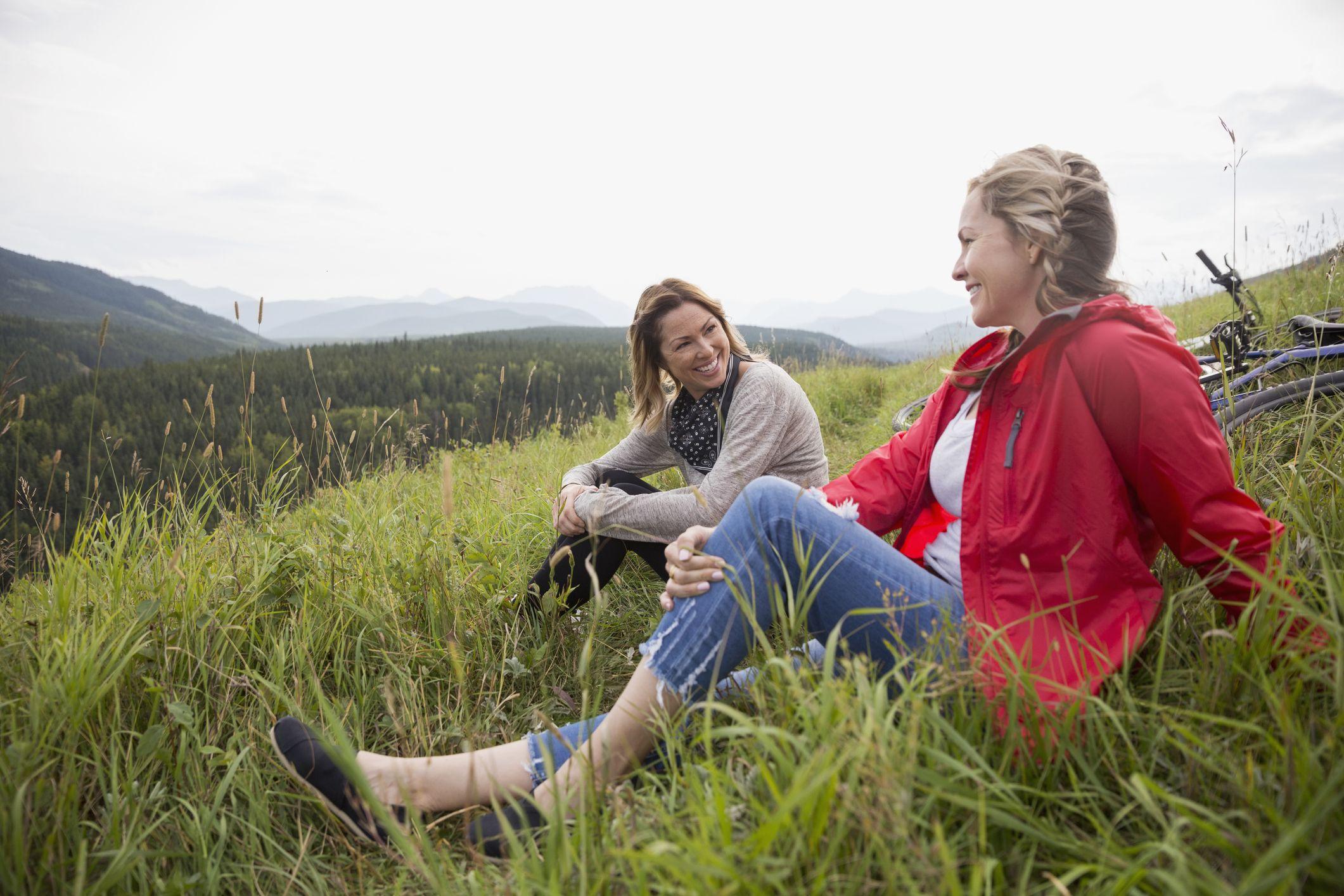 Female friends relaxing in grass in remote rural field