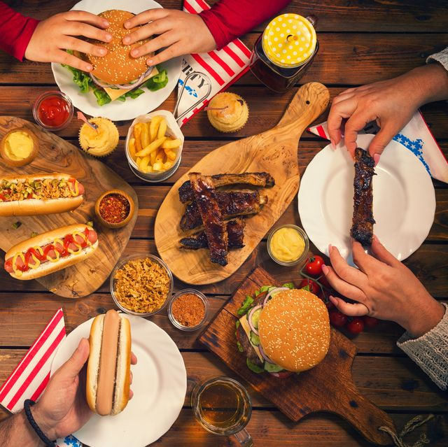 young family celebrating 4th of july, they having traditional lunch at the picnic