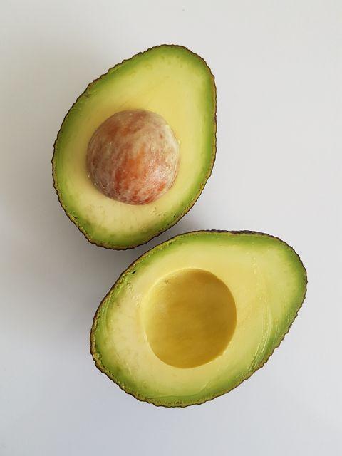 Directly Above Shot Of Halved Avocado On White Background