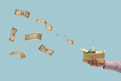 Money flying off stack of bills in man's hand