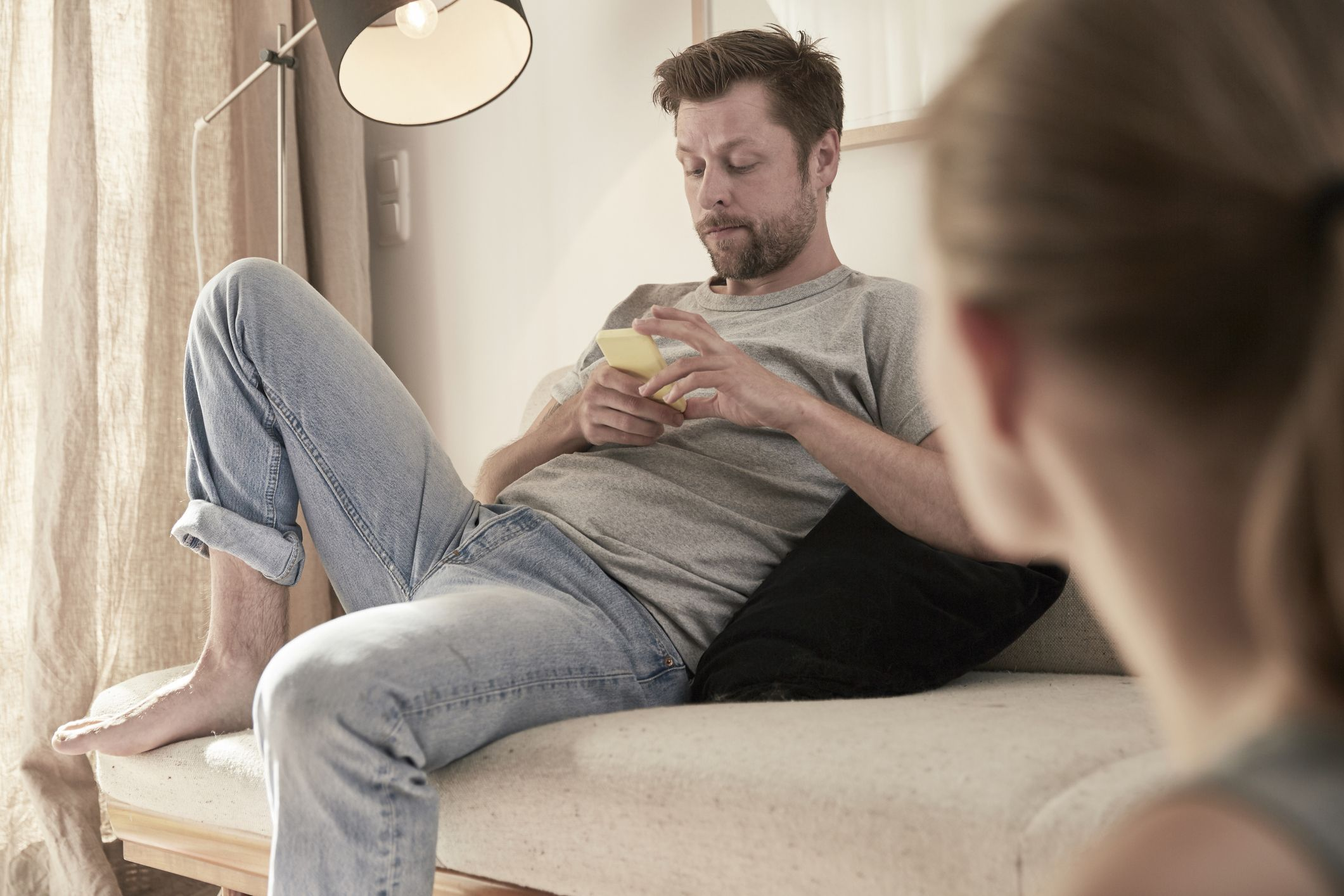 Man at home sitting on couch looking at cell phone with women in foreground