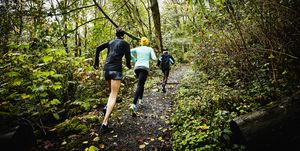 Group of female friends running up forest trail