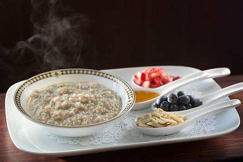 steaming steel cut oatmeal porridge with toppings at breakfast