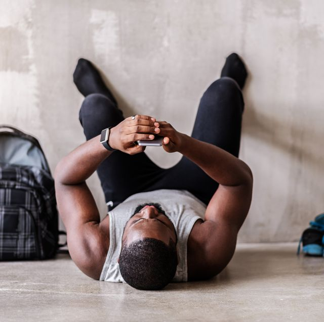 end of training tired african muscular man is lying on floor and looking to his mobile phone he is resting with barefoot legs on wall