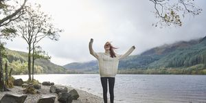 Woman laughing by the side of a loch