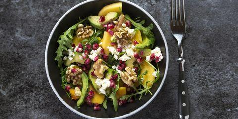 bowl of avocado salad with rocket, pomegranate seed, kaki, feta and walnuts