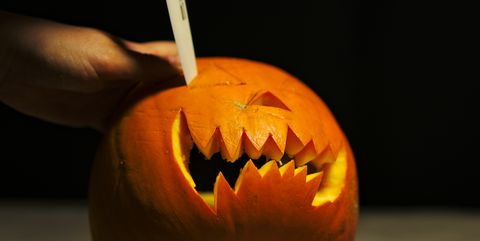 Cropped Image Of Person Carving Pumpkin At Table