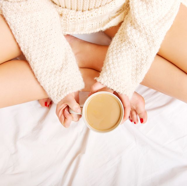 Low Section Of Woman Holding Cup With Coffee On Bed At Home