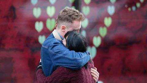 a couple hug at the police corden at the north end of london bridge in london on june 4, 2017, after leaving a bunch of flowers in tribute to the victims of the june 3 terror attack 