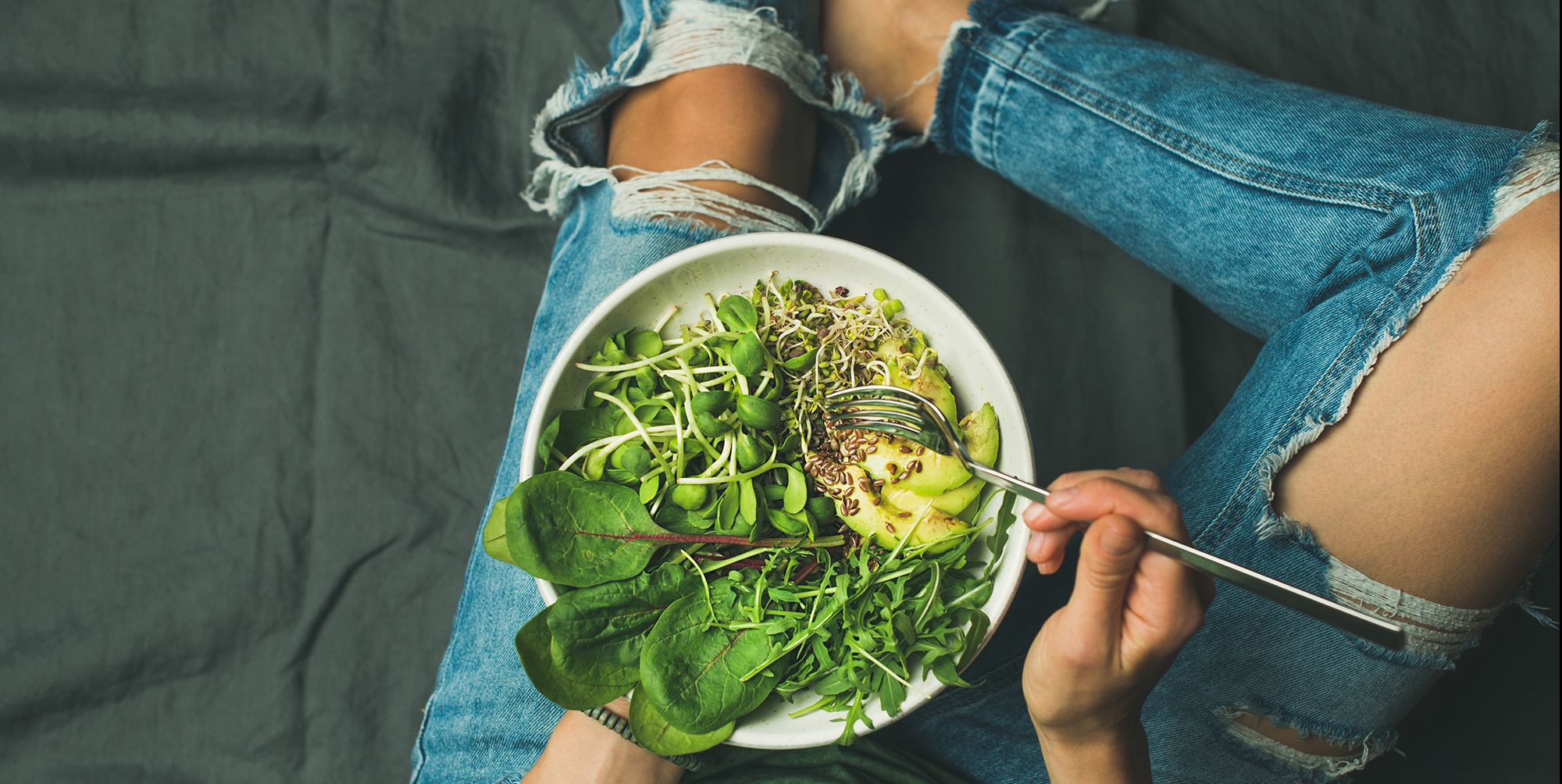 Vegetarian breakfast bowl with spinach, arugula, avocado, seeds and sprouts