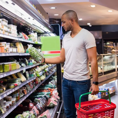 young african man buying vegetables in grocery section at supermarket black man choose vegetables in the supermarket while holding grocery basket man shopping veggies at supermarket