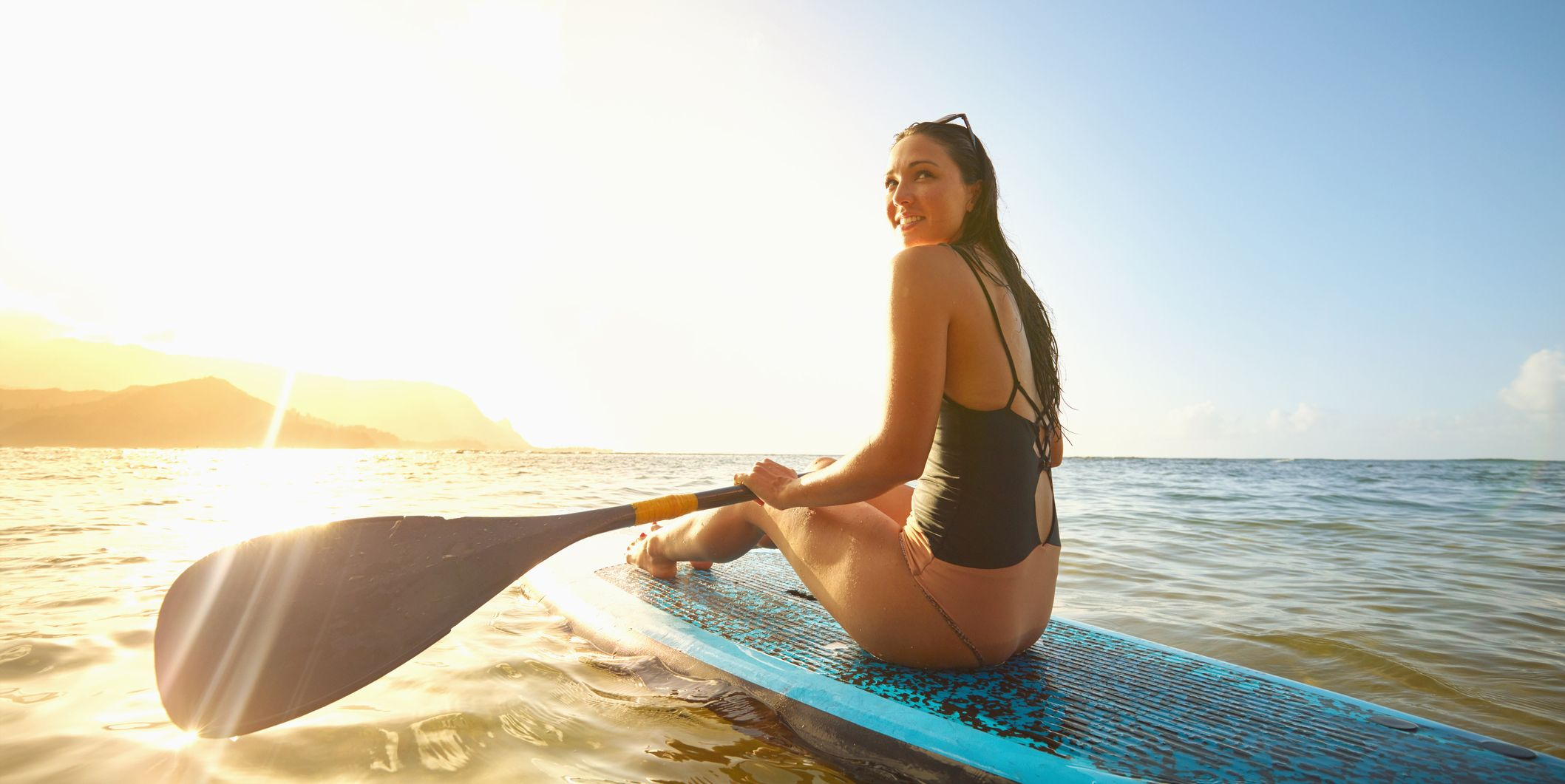 Mixed Race woman sitting on paddleboard in ocean