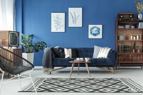 blue up to date decor of lounge with blue sofa and patterned carpet