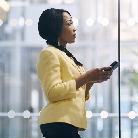 Creative businesswoman texting on cell phone in office