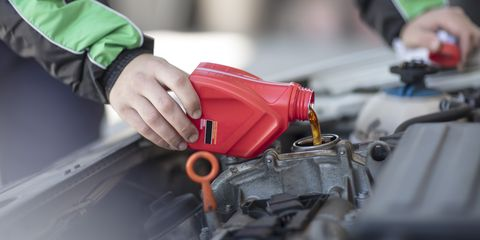 Man filling up car with motor oil
