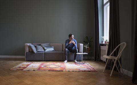 Man sitting on couch at home looking through window