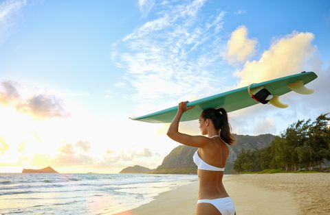 Pacific Islander woman standing on beach holding surfboard