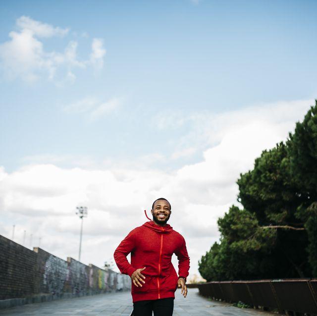 lachende jonge man aan het hardlopen op de straat in een rode trui