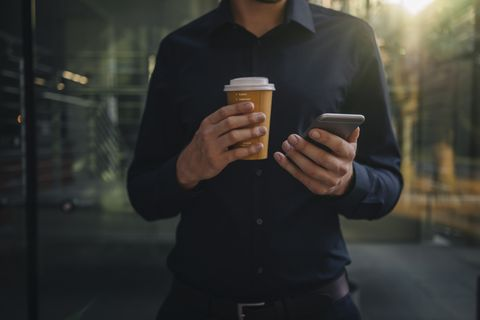 guy carrying coffee and a phone