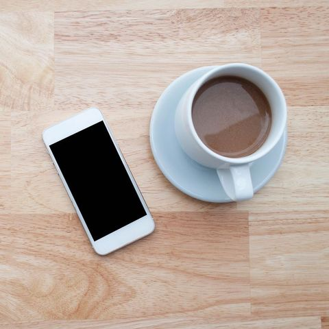 High Angle View Of Fresh Latte Served By Mobile Phone On Table
