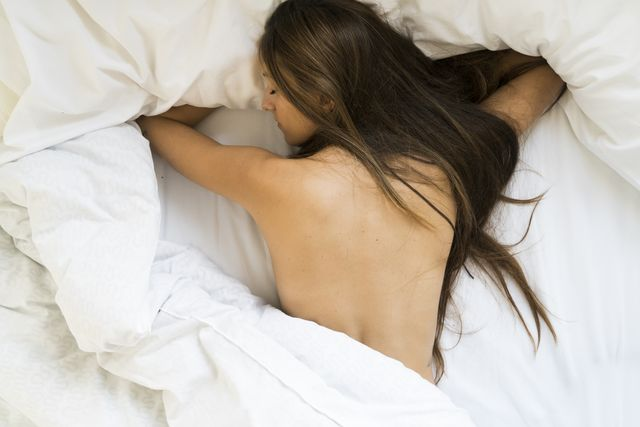 Top view of nude young woman lying in bed