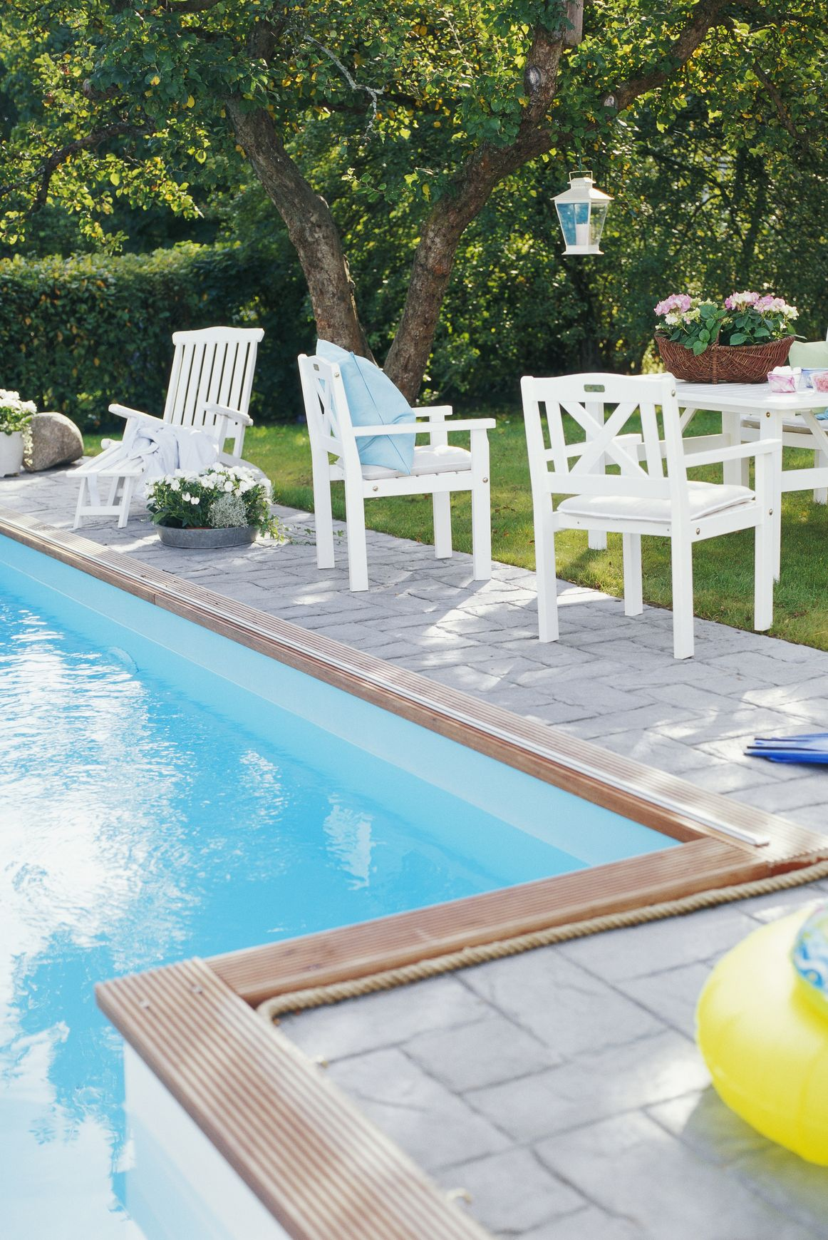 Outdoor furniture by a pool.