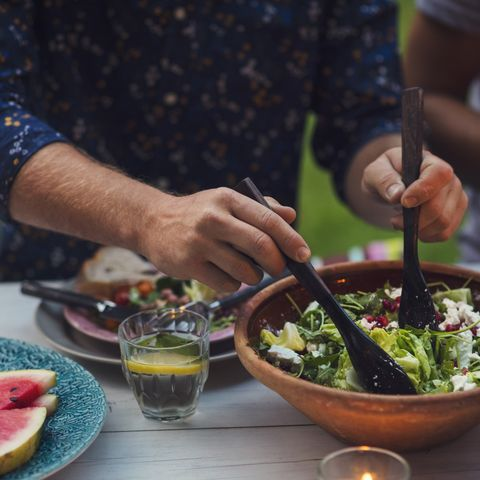 midsection of man mixing salad at table during garden party mens health weight loss tips