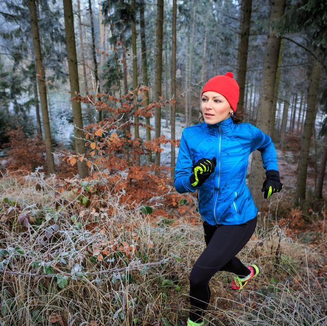vrouw in de kou aan het hardlopen in het bos