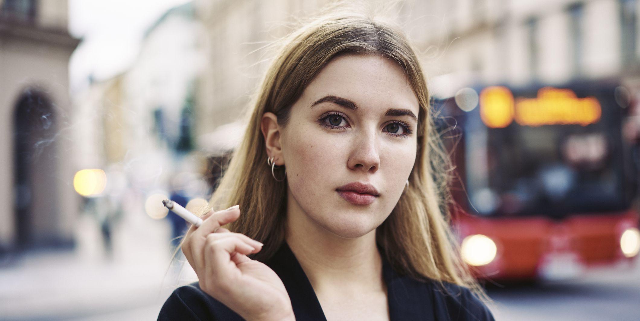 """Sweden, Uppland, Stockholm, Kungsholmen, Portrait of young woman smoking in street"""