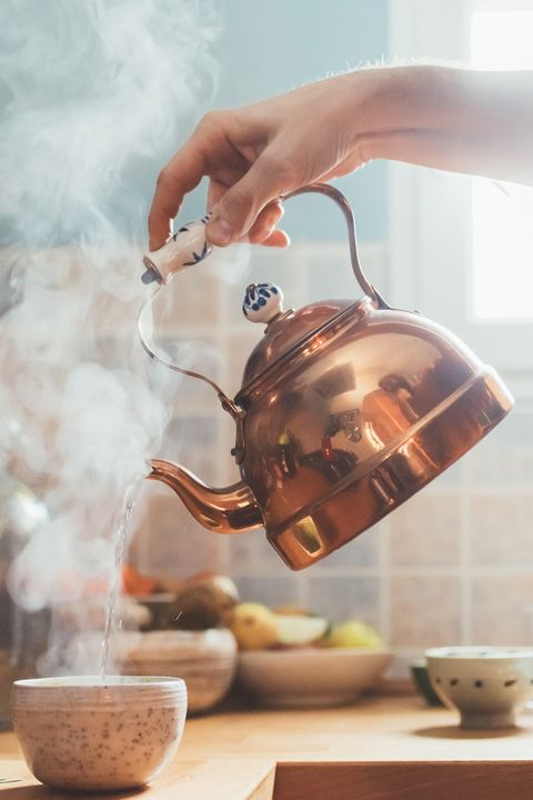 arm of man pouring boiling water into bowl in kitchen