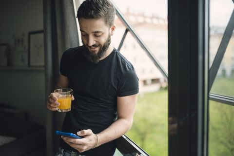 Young man drinking an orange juice and using his smartphone at the window